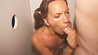 Slut Wife in the Gloryhole Sucking Cocks While Being Fucked